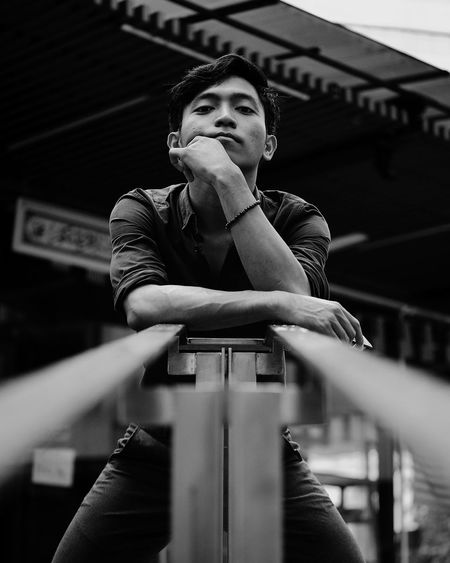 Low angle portrait of young man standing by railing