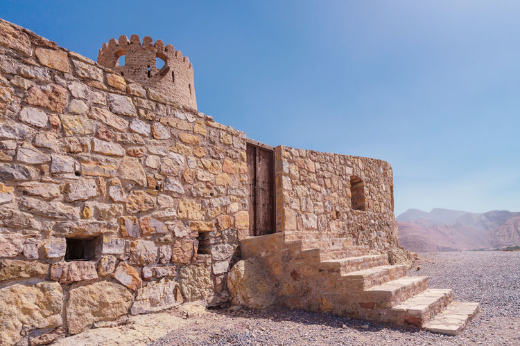 Stone wall of a small medieval arabian fort with wooden door and stone stairs the desert.