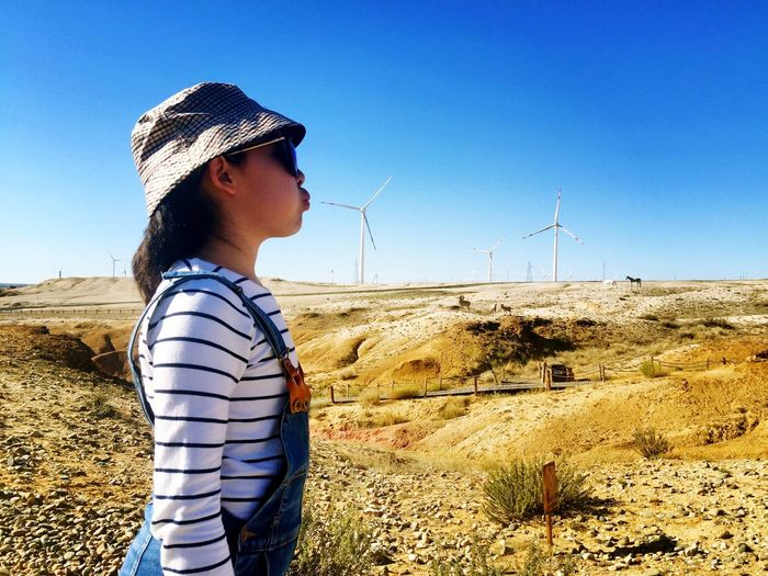 Optical illusion of girl blowing windmill while standing on land