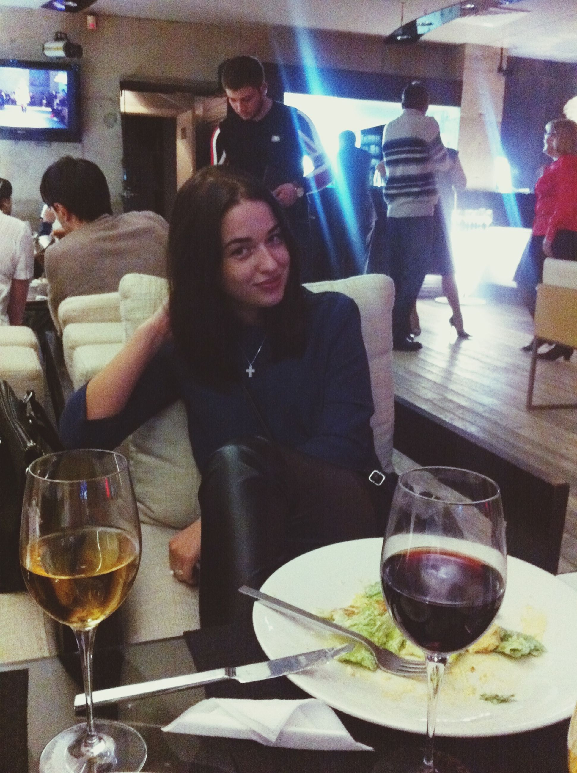 indoors, lifestyles, food and drink, drink, leisure activity, person, restaurant, table, casual clothing, young adult, sitting, drinking glass, alcohol, refreshment, front view, standing, glass - material, wineglass