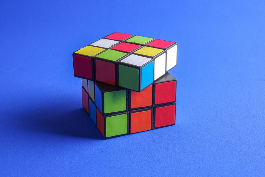 RUBIK'S CUBE , CREATIVITY TOY Creativity Rubik Cube Block Blue Blue Background Close-up Colored Background Copy Space Cube Shape Cut Out Design Geometric Shape Indoors  Intelligence Multi Colored No People Red Rubik Shape Single Object Still Life Studio Shot Toy Toy Block
