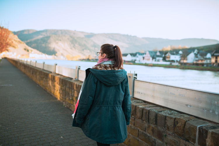 Rear view of woman walking by a river