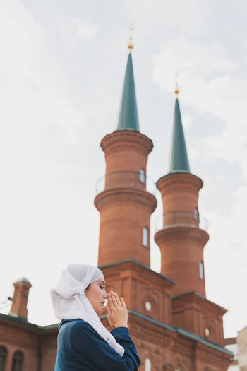 Low angle view of woman praying against mosque