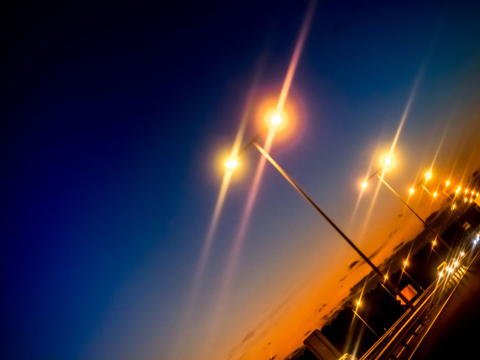Low angle view of illuminated street lights against sky at night