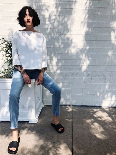 One Person Casual Clothing Real People Full Length Leisure Activity Shadow Urban Fashion Jungle Sunlight Lifestyles Young Adult Wall - Building Feature Front View Architecture Day Women Sitting Looking Fashion Standing Jeans Young Women