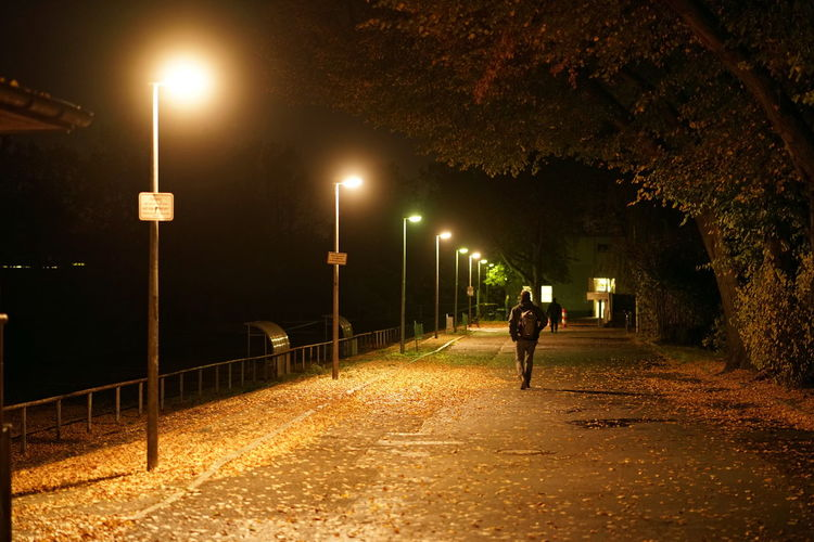 Illuminated Street Night Street Light One Person Direction Plant Lighting Equipment Walking The Way Forward Tree Footpath City Nature Transportation Full Length Architecture Motion Road Outdoors Alley