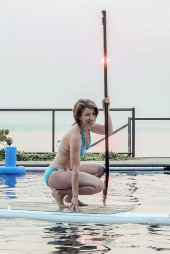 Woman kneeling on a paddle board while floating in a pool wearing a turquoise bikini. Adult Beautiful Woman Clear Sky Day Fitness Full Length Happiness Hazy  Leisure Activity Lifestyles Looking At Camera Middle Aged Nature One Person Outdoors People Portrait Railing Real People Sitting Sky Sky And Clouds Smiling Swimming Pool Water