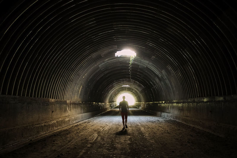 Tunnel Architecture Direction One Person The Way Forward Full Length Illuminated Walking Built Structure Arch Rear View Night Standing Real People Lighting Equipment Dark Adult Transportation Footpath Light At The End Of The Tunnel Outdoors Diminishing Perspective