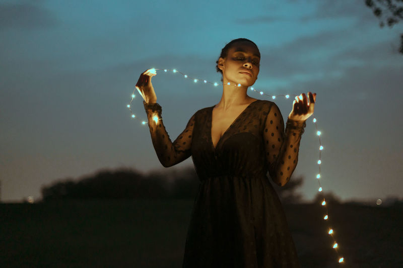 Beautiful woman with holding string lights outdoors at dusk