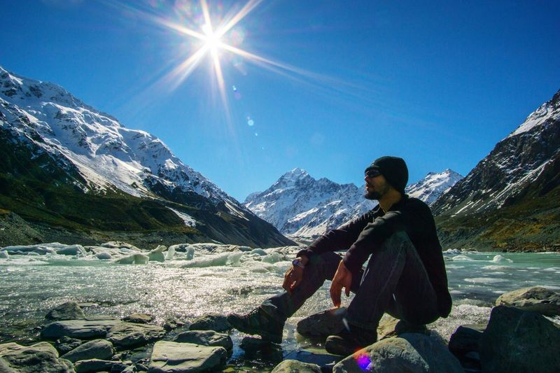Side view full length of man sitting on rock by river against mt cook during winter