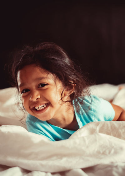 Portrait of smiling girl on bed at home