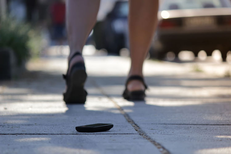 Mobile phone on sidewalk with woman walking in background
