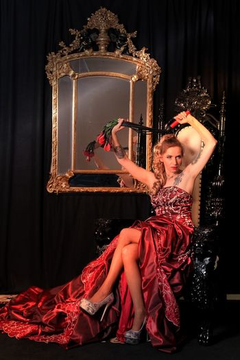 Sensuous young woman in red dress holding whip while sitting on throne