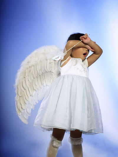 Girl in angel costume against purple background