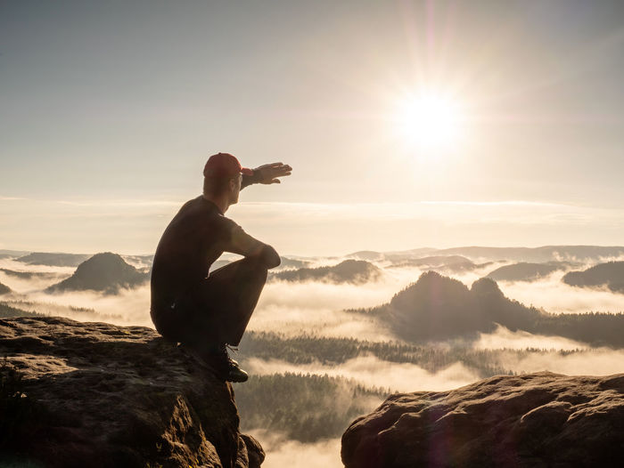 Man sitting in foggy morning. sit squatting on the peak edge and enjoy view valley during heavy mist