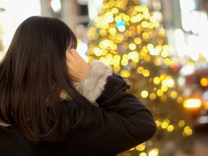 Christmas Rear View Christmas Tree Long Hair Tree Warm Clothing Focus On Foreground One Person Women Night Close-up Winter Lifestyles Illuminated Real People