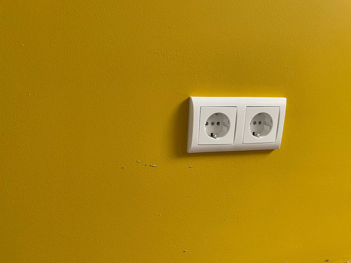 Close-up of telephone mounted on yellow wall