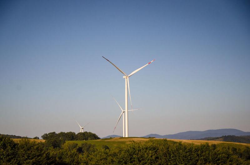 Wind turbines on field against clear sky