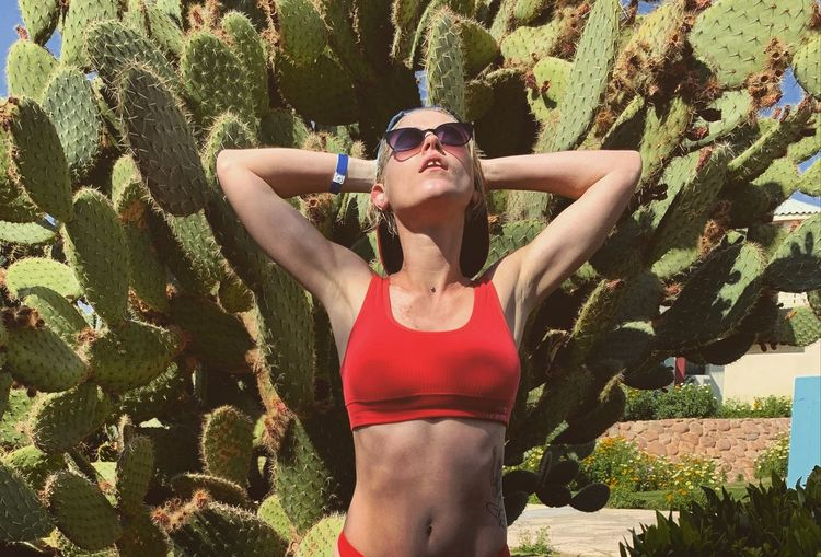 Young woman standing against cactus plant