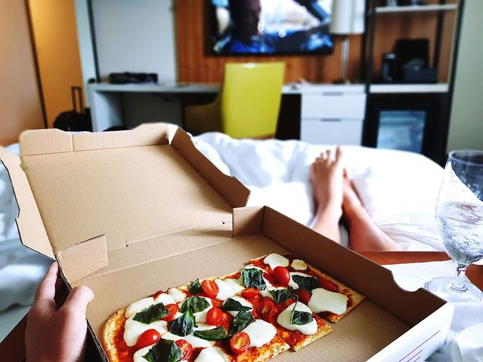 Midsection Of Woman With Pizza On Bed At Home
