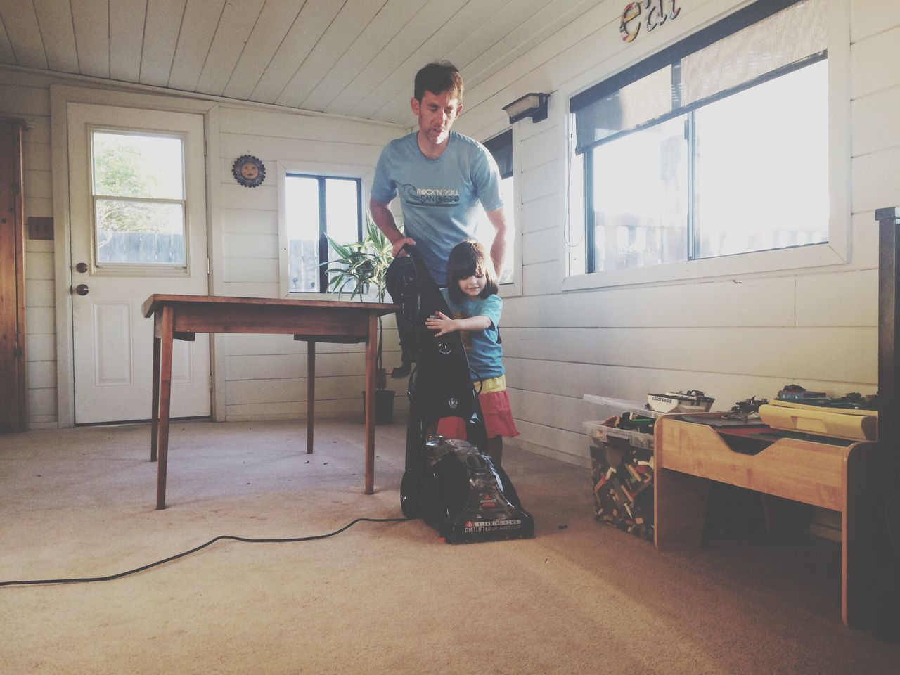 Father and girl with vacuum cleaner at home