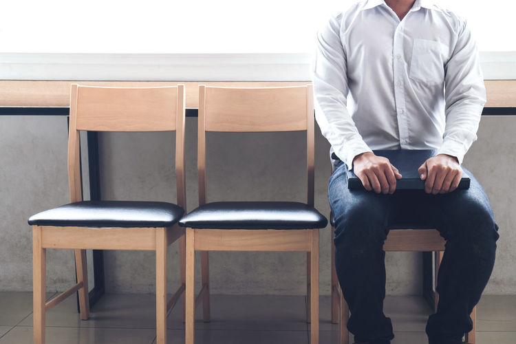 Midsection of man sitting on chair
