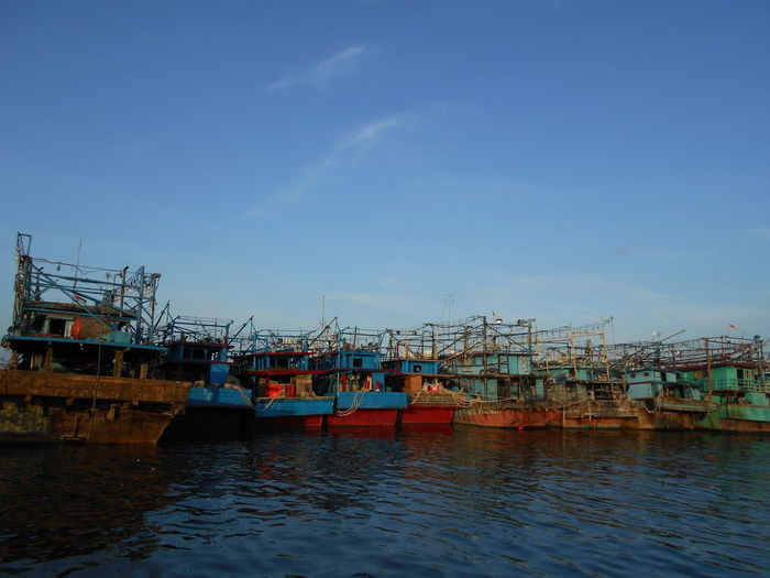 Fishing boats moored at harbor against blue sky