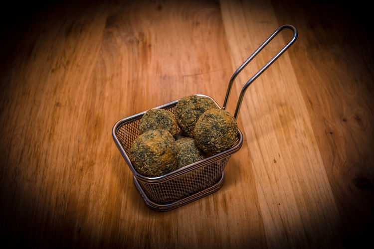 Close up of delicious meatballs on steel food basket, they can be made with meat, vegetables, fish. Food And Drink Wood - Material Food Indoors  No People Kitchen Utensil Vignette Wellbeing Healthy Eating Table Freshness Wood Close-up High Angle View Wood Grain Studio Shot Spoon Brown Background Eating Utensil Nature Crockery Vegetarian Food