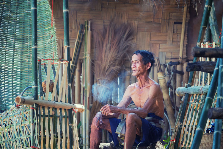 Thailand Father old man smoking after working hand made Basket bamboo or fishing gear. Local life country Thailand Alone Smoking Adult Adults Only Casual Clothing Chair Day Happiness Mature Adult One Person One Woman Only Only Women Outdoors People Real People Senior Adult Sitting Smiling