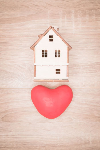 Close-Up Of Model Home And Heart Shape On Wooden Table