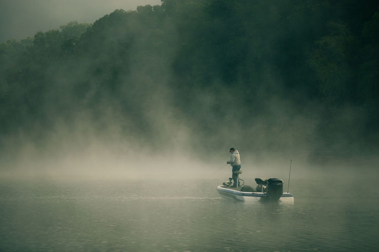 Rear view of man fishing at lake during foggy weather