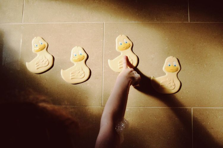 Cropped image of girl pointing at duck toy stuck on wall