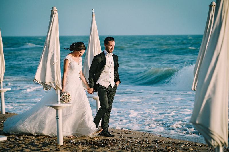 Bride And Bridegroom Walking On Shore At Beach