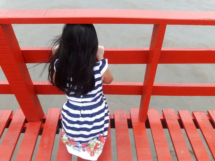 High Angle View Of Girl Standing On Red Footbridge Over River