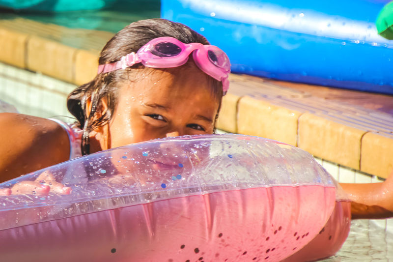 portrait of a young girl relaxing in the pool on pink inflatable Water One Person Pool Swimming Pool Lifestyles Leisure Activity Real People Childhood Headshot Child Portrait Swimwear Wet Girls Enjoyment Inflatable  Fun Pink Color Outdoors Innocence Hairstyle Human Face Diversity Swimming Goggles