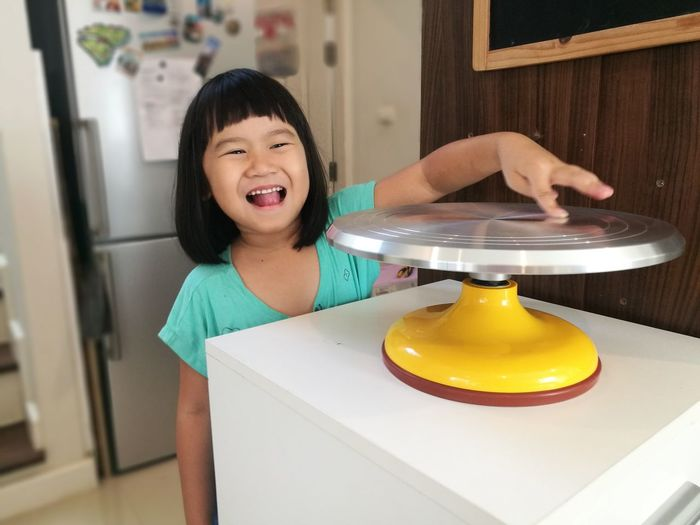 Portrait Of Cheerful Girl Touching Cakestand On Table At Home