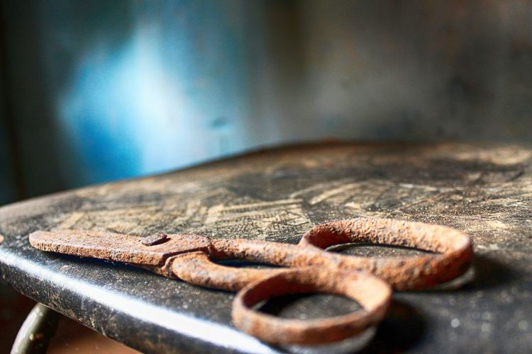 Close-Up Of Rusty Scissor On Table