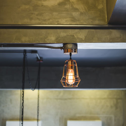 Illuminated pendant light hanging from ceiling at home