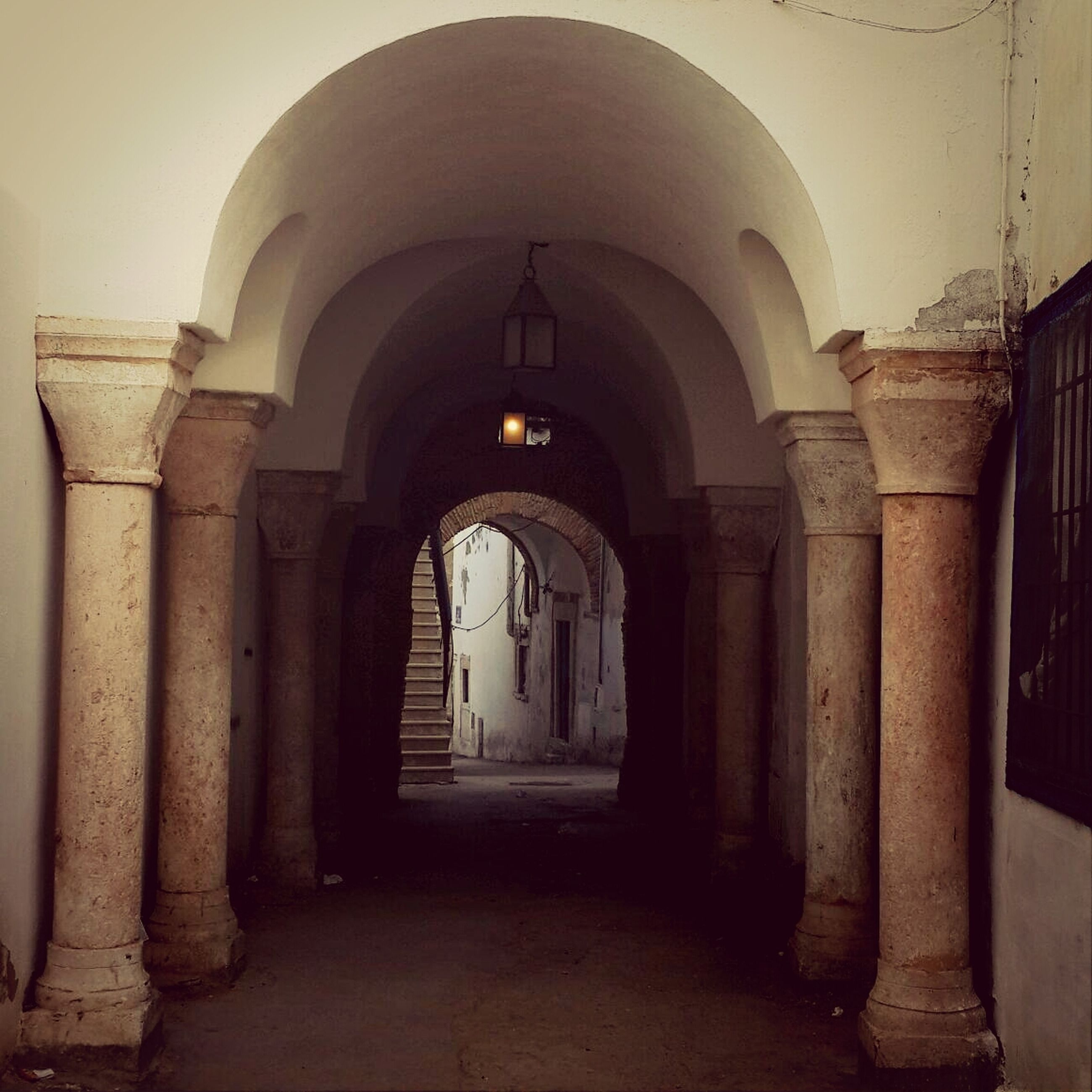 arch, architecture, built structure, religion, place of worship, church, spirituality, indoors, history, entrance, architectural column, building exterior, corridor, cathedral, travel destinations, column, archway, famous place