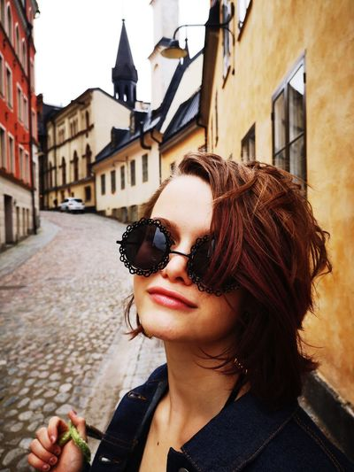 Portrait of girl wearing sunglasses on street amidst buildings in city