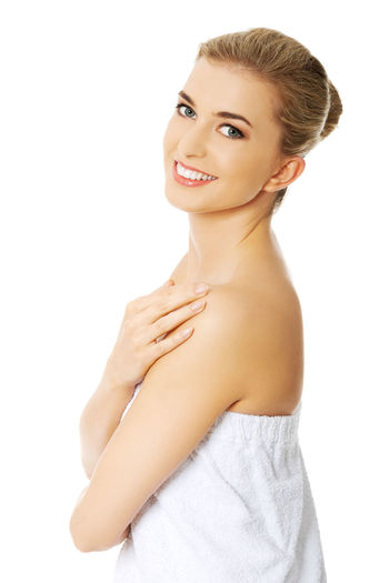 Portrait Of Smiling Woman Wrapped In Towel Against White Background