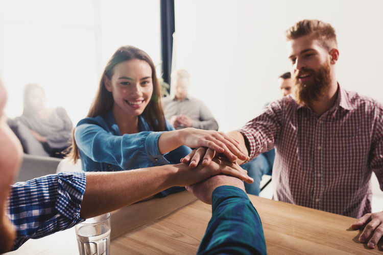 Business people stacking hands at office