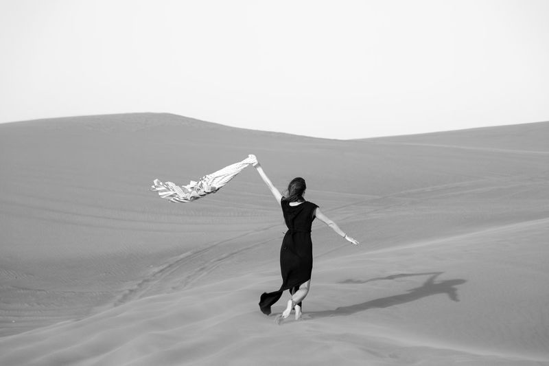 Rear view of woman walking at desert against clear sky