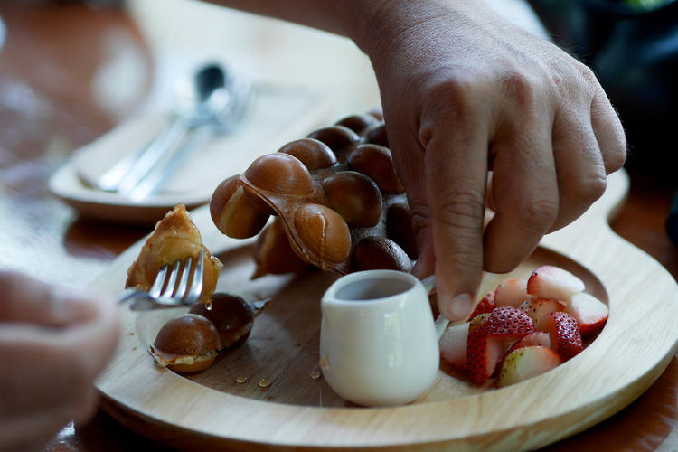 Midsection of person having breakfast on table