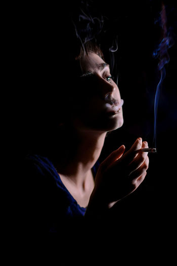 Margo, January 2019 Cigarette  Smoking Issues Smoke - Physical Structure Headshot Portrait Dark Contemplation One Person Black Background Indoors  Portrait Of A Woman Portrait Photography Smoking Fume Composition Art Young Adult EyeEm Best Shots EyeEmNewHere Dark Night Nightphotography Beautiful Conceptual Minimalism