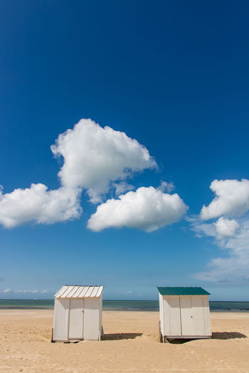 Beach huts at beach against blue sky