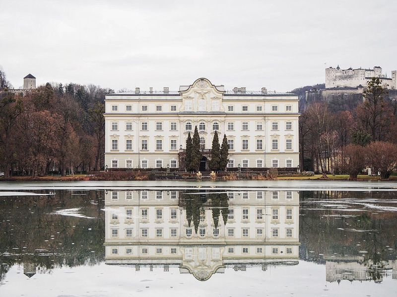 Salzburg, Austria. Across the frosty lake Leopoldskroner Weiher is Schloss Leopoldskron, the home of the von Trapp family in the Sound of Music. Schloss Leopoldskron Travel Salzburg Austria Film Location Sound Of Music Winter Palace