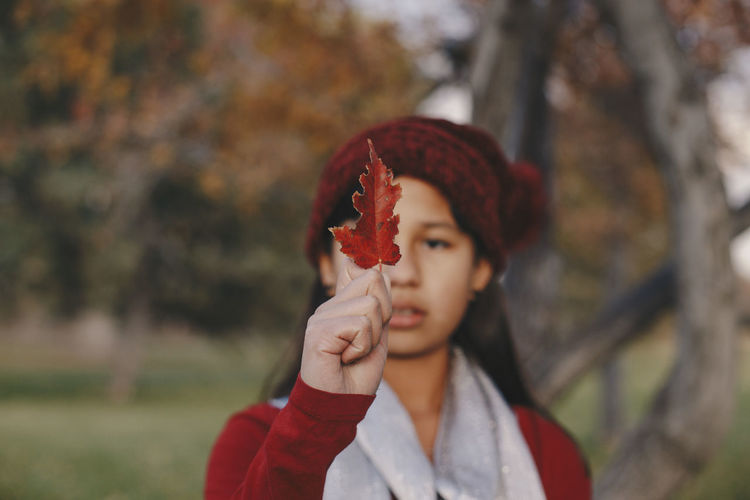 Portrait of young woman holding red leaf outdoors