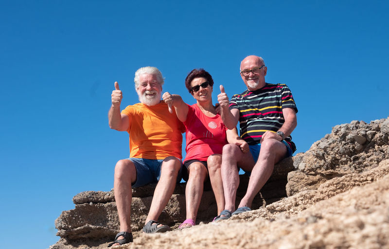 Low angle view portrait of senior friends gesturing while sitting on rock against sky