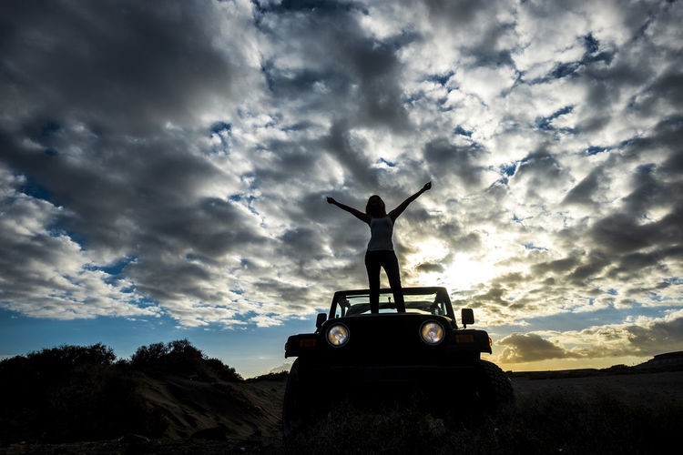 Low Angle View Of Woman With Arms Raised Standing On Off-Road Vehicle At Sunset
